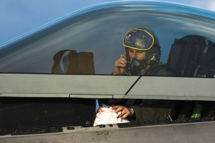 An F-22 Raptor fighter aircraft pilot assigned to the 95th Fighter Squadron at Tyndall Air Force Base, Fla., prepares to exit an F-22 at Spangdahlem Air Base, Germany, Aug. 28, 2015. The U.S. Air Force deployed four F-22 Raptors, one C-17 Globemaster III and more than 50 Airmen to Spangdahlem in support of the first F-22 European training deployment. The inaugural F-22 training deployment to Europe is funded by the European Reassurance Initiative, a $1 billion pledge announced by President Barack Obama in March 2014. (U.S. Air Force photo by Airman 1st Class Luke Kitterman/Released)