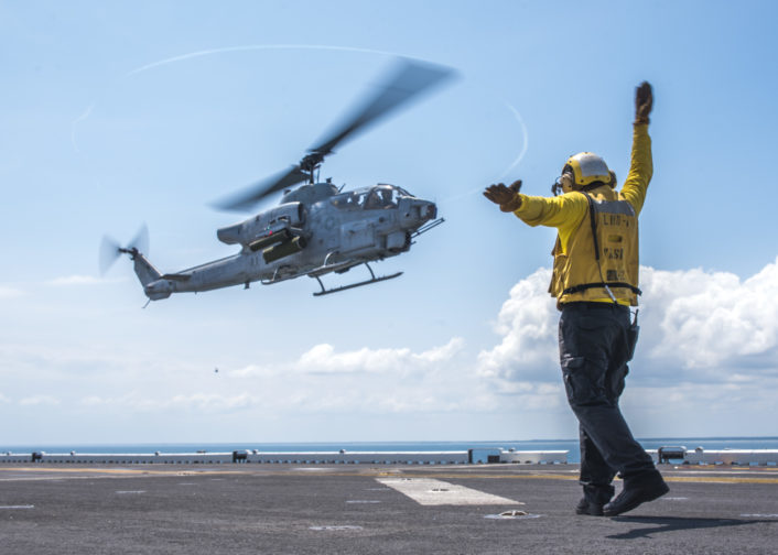 160626-N-JW440-229 ATLANTIC OCEAN (June 26, 2016) Aviation Boatswain's Mate (Handling) 3rd Class Markgerald Zagala signals an AH-1W Super Cobra to land aboard the amphibious assault ship USS Wasp (LHD 1). Wasp is deployed with the Wasp Amphibious Ready Group to support maritime security and theater security cooperation efforts in the U.S. 5th and 6th Fleet areas of operation. (U.S. Navy photo by Mass Communication Specialist 3rd Class Rawad Madanat/Released)