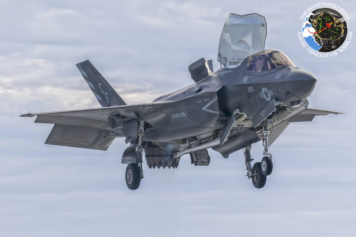 F-35B of USMC VMFA-211 hovers aside the USS America as it prepares for a vertical landing on deck during the integrated USN/USMC proof of concept demonstration November 19, 2016.