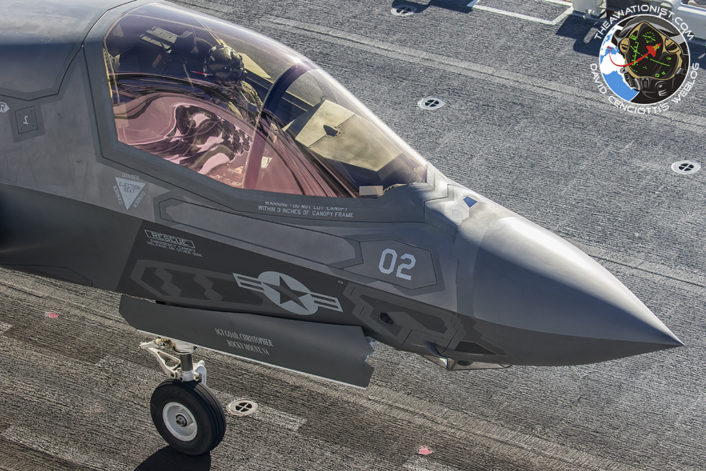 "F-35B from VMFA-211 taxis to take off postion on the deck of the USS America (LHA-16 during proof of concept demonstration November19. The American Flag graphic on the America's ""Conning Tower"" is reflected in the F-35Bs canopy."